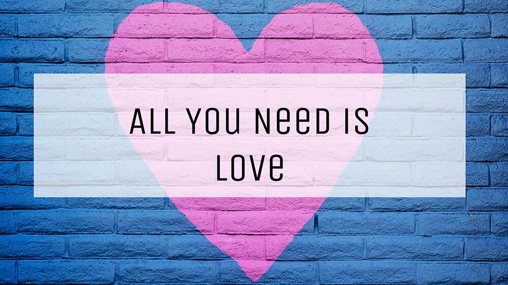 """Ein rosa Herz auf einer blauen Backsteinwand. Darüber befindet sich ein weißes halb transparentes weißes Rechteck. Auf diesem befindet sich ein schwarzer Schriftzug """"All you need is love"""" - Perfekt für die Kontakt-Seite"""